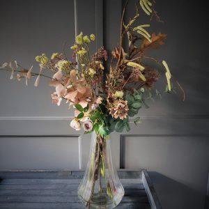 prachtig herfst boeket van kunstbloemen in een mooie glazen vaas