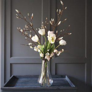 mooie magnoliatakken en frisse tulpen gecombineerd in een prachtig voorjaarsboeket