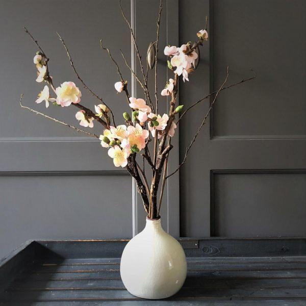 prachtige lichtroze bloesemtakken in een lief vaasje